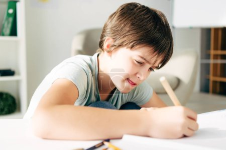 Photo for Kid with dyslexia drawing with pencil and sitting at table - Royalty Free Image
