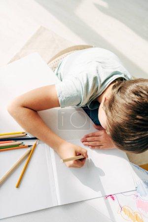 Photo pour Vue de dessus de l'enfant avec dessin dyslexie avec crayon - image libre de droit