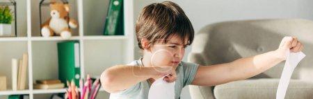 Photo pour Plan panoramique de gamin irrité avec papier perforant dyslexie - image libre de droit