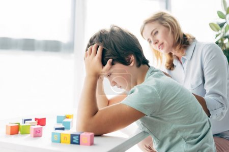Photo for Side view of sad kid with dyslexia looking at building blocks and child psychologist looking at him - Royalty Free Image