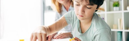 Photo for Panoramic shot of kid with dyslexia sitting at table - Royalty Free Image