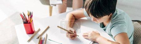 Photo pour Plan panoramique de l'enfant avec dyslexie dessin sur papier avec crayon - image libre de droit