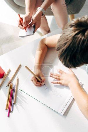 Photo pour Vue recadrée de l'enfant avec dyslexie dessin sur papier avec crayon - image libre de droit