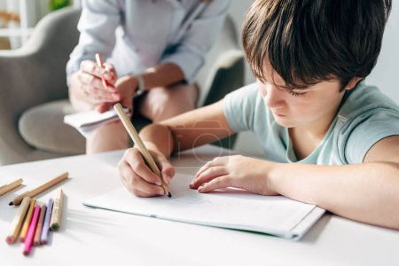 Photo for Selective focus of kid with dyslexia drawing on paper with pencil - Royalty Free Image