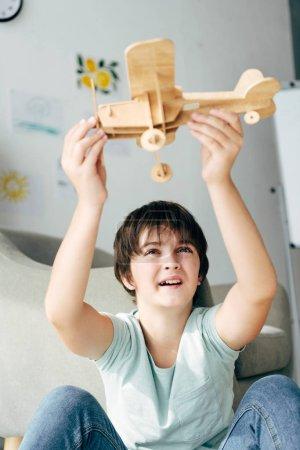 Photo pour Mignon enfant avec dyslexie jouer avec avion en bois - image libre de droit