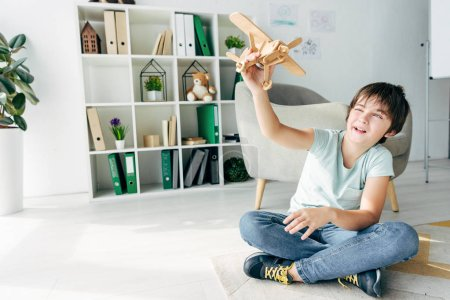 Photo for Cute kid with dyslexia sitting on floor and playing with wooden plane - Royalty Free Image