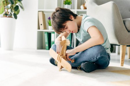 Photo for Kid with dyslexia sitting on floor and holding wooden plane - Royalty Free Image