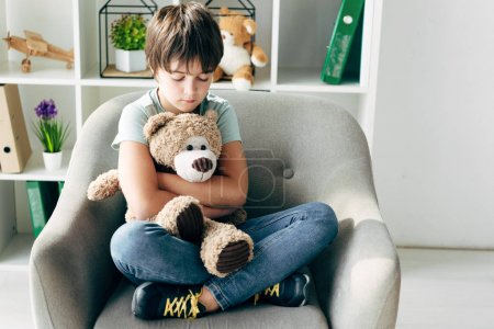Photo for Kid with dyslexia holding teddy bear and sitting on armchair - Royalty Free Image