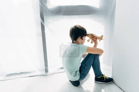 Photo for High angle view of kid with dyslexia sitting on floor and playing with wooden plane - Royalty Free Image