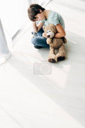 Foto de Vista de gran angular del niño con dislexia sentada en el suelo con oso teddy. - Imagen libre de derechos