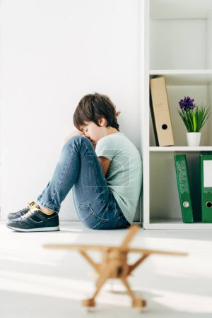Photo for Selective focus of sad kid with dyslexia sitting on floor - Royalty Free Image