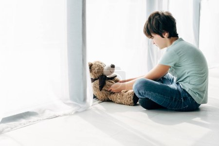 Photo for Kid with dyslexia sitting on floor and looking at teddy bear - Royalty Free Image
