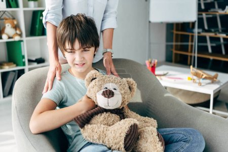 Photo for Cropped view of child psychologist hugging kid with dyslexia holding teddy bear - Royalty Free Image