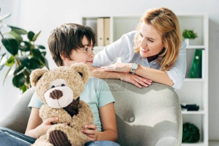 Photo for Kid with dyslexia holding teddy bear and child psychologist talking with him - Royalty Free Image