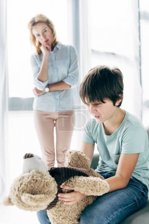 Photo for Sad kid with dyslexia holding teddy bear and child psychologist looking at him - Royalty Free Image