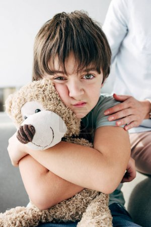 Photo for Kid with dyslexia holding teddy bear and child psychologist hugging him - Royalty Free Image