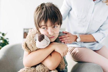 Foto de Triste niño con dislexia sosteniendo osito de peluche y niño psicólogo abrazándolo - Imagen libre de derechos
