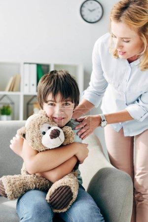 Photo pour Enfant souriant avec dyslexie tenant ours en peluche et psychologue enfant le regardant - image libre de droit