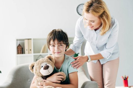 Photo for Smiling kid with dyslexia holding teddy bear and child psychologist looking at him - Royalty Free Image