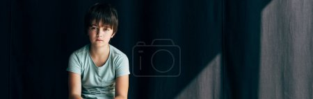 Photo for Panoramic shot of kid with dyslexia looking at camera on black background - Royalty Free Image