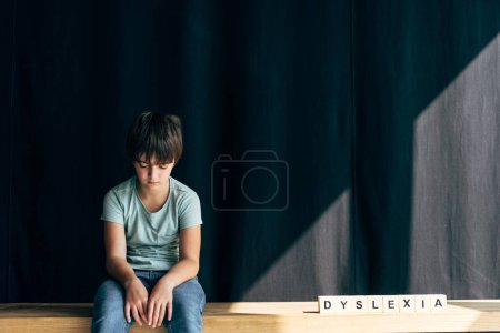 Photo for Sad kid with dyslexia sitting near wooden cubes with lettering dyslexia on black background - Royalty Free Image