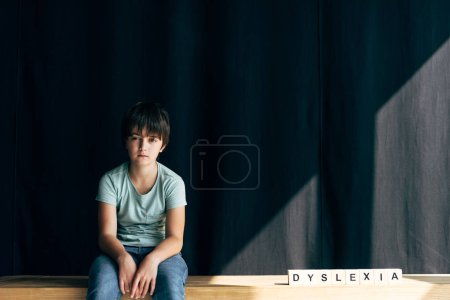 Photo for Kid with dyslexia looking at camera and sitting near wooden cubes with lettering dyslexia - Royalty Free Image
