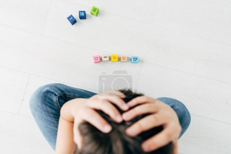 Photo for Top view of sad kid with dyslexia sitting near building blocks - Royalty Free Image