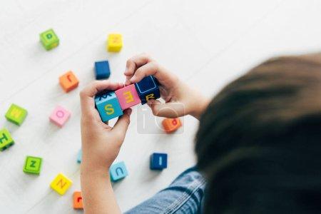 Photo pour Vue recadrée de l'enfant avec dyslexie jouer avec des blocs de construction colorés - image libre de droit