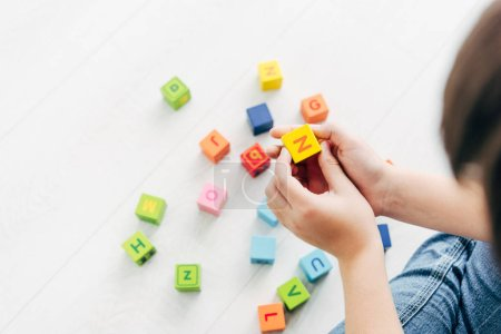 Photo for Cropped view of kid with dyslexia playing with colorful building blocks - Royalty Free Image