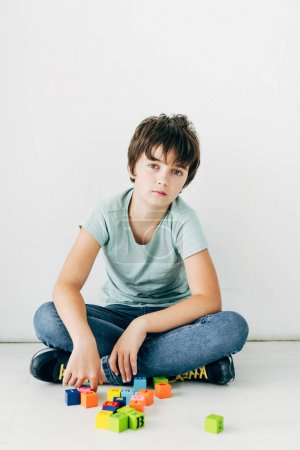 Photo for Kid with dyslexia sitting on floor with building blocks on white background - Royalty Free Image