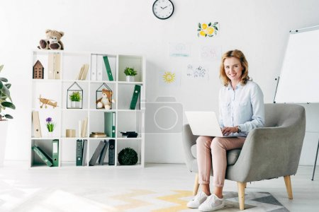 Photo for Attractive and smiling child psychologist in shirt holding laptop and sitting on armchair - Royalty Free Image