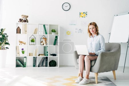 Photo for Attractive child psychologist in shirt holding laptop and sitting on armchair - Royalty Free Image