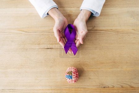 Photo for Cropped view of doctor holding purple ribbon in clinic - Royalty Free Image
