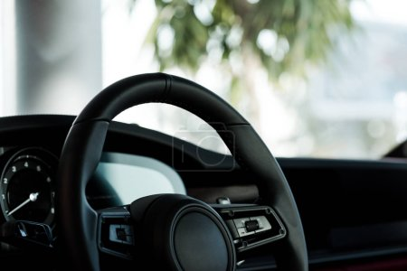 KYIV, UKRAINE - OCTOBER 7, 2019: buttons on black leather steering wheel in modern porshe
