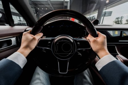 Photo for KYIV, UKRAINE - OCTOBER 7, 2019: cropped view of driver holding steering wheel while sitting in modern porshe - Royalty Free Image