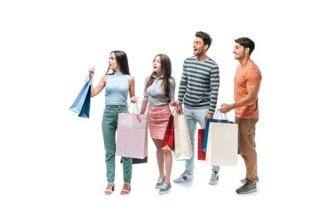 Photo pour Amis choqués marchant avec des sacs à provisions ensemble, isolé sur blanc - image libre de droit