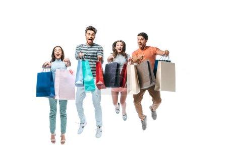 Photo pour Amis excités sautillant et tenant des sacs à provisions avec des enseignes de vente, isolés sur blanc - image libre de droit