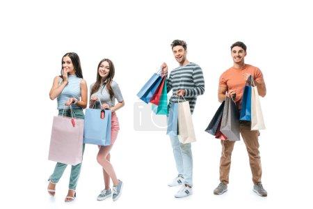 Photo pour Amis positifs tenant des sacs à provisions avec des enseignes de vente, isolés sur blanc - image libre de droit