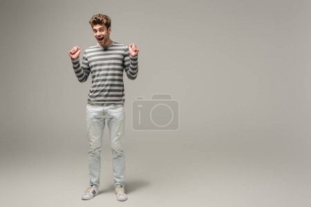 Photo for Excited man cheering and standing on grey - Royalty Free Image