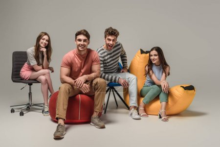 Photo for Smiling friends sitting on different chairs, on grey - Royalty Free Image