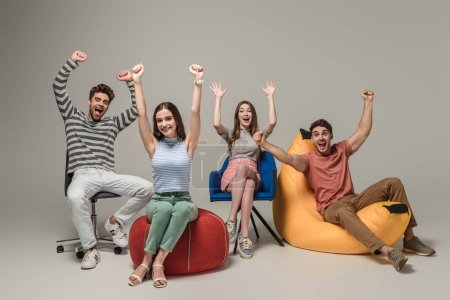 Photo for Emotional cheering friends sitting on different chairs, on grey - Royalty Free Image