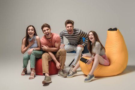 Photo for Emotional friends laughing and sitting on different chairs, on grey - Royalty Free Image