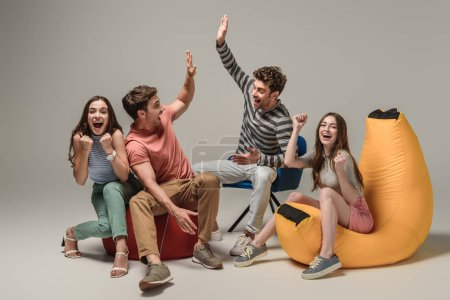 excited friends giving highfive while sitting on different chairs, on grey