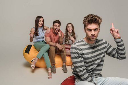 angry man showing middle finger to friends sitting on bin bag chair together, on grey