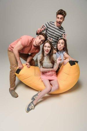 Photo pour Des amis joyeux qui sortent la langue, qui montrent des signes de victoire et qui s'amusent sur une chaise de sac, sur un gris - image libre de droit