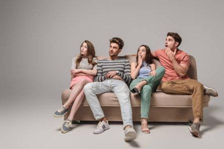 Schockierte junge Freunde sitzen zusammen auf Sofa in Grau