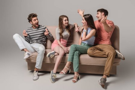 Photo for Emotional young friends talking and sitting on sofa on grey - Royalty Free Image