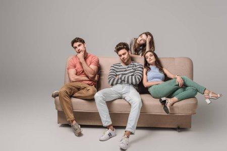 amigos aburridos y pensativos sentados juntos en el sofá en gris