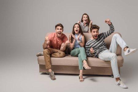 fröhliche junge Freunde jubeln und sitzen auf dem Sofa auf grau