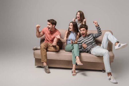 Photo for Excited young friends cheering and sitting on sofa on grey - Royalty Free Image